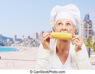 portrait of senior cook woman eating corn cob against a beach