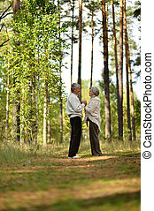 Portrait of senior couple have a walk in autumn forest