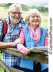 Portrait Of Senior Couple Hiking In Countryside With Map