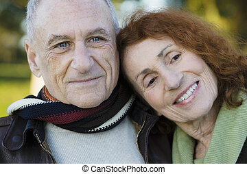 Portrait of Two Happy Seniors Leaning on Each Other