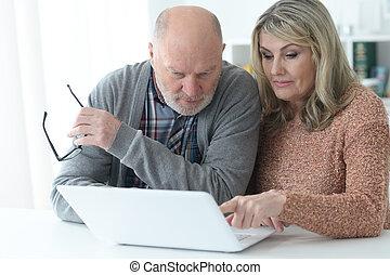 Portrait of senior couple portrait with laptop