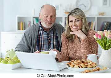 Portrait of senior couple with laptop during breakfast