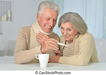 couple with thermometer at home