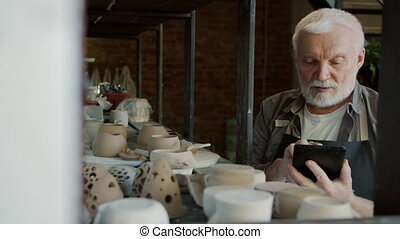 Portrait of senior craftsman counting hand-made pots in ...