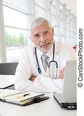 Portrait of senior doctor in office