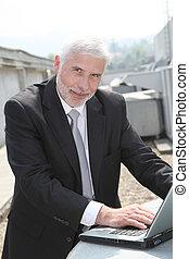 Portrait of senior man checking industrial setup