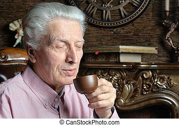 Portrait of senior man drinking tea