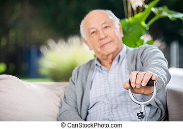 Portrait Of Senior Man Holding Metal Cane