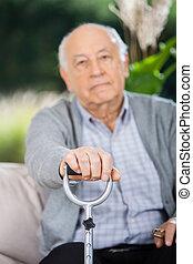 Portrait Of Senior Man Holding Metal Walking Stick