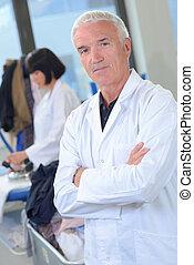 Portrait of senior man in white coat