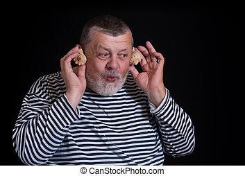 Portrait of senior man joying as a kid listening sounds of sea shell