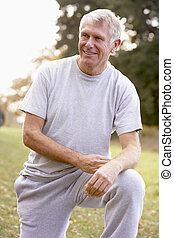 Portrait Of Senior Man Kneeling In Park