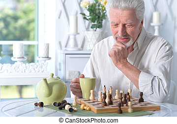 Portrait of senior man looking at chess board