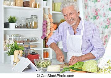 Portrait of senior man preparing dinner in kitchen