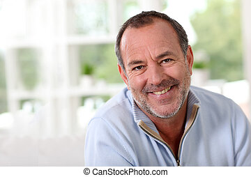 Portrait of senior man sitting in sofa at home
