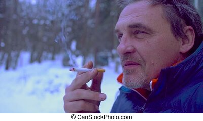 Portrait of senior man smoking a cigarette and talking