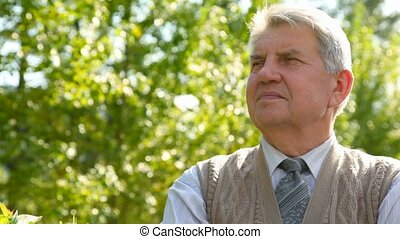 portrait of senior man, tree in background