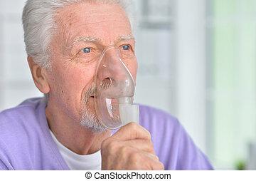 Portrait of senior man with inhaler at home