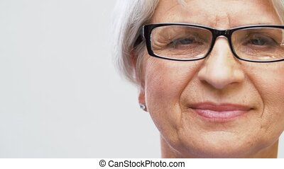 portrait of senior woman adjusting her glasses - vision and...