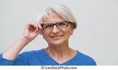 portrait of senior woman adjusting her glasses - vision and...