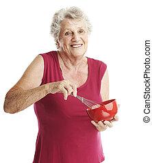 senior woman beating eggs