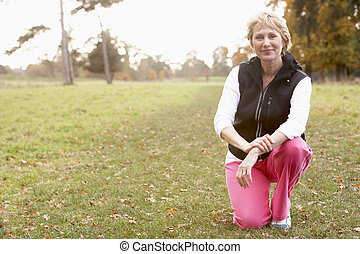 Portrait Of Senior Woman Crouching In The Park