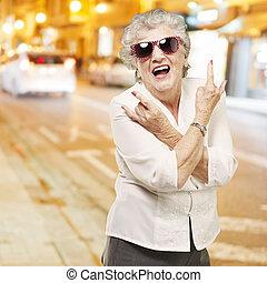 portrait of senior woman doing rock symbol against a city night