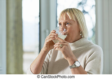 Portrait of senior woman having breakfast with milk -...
