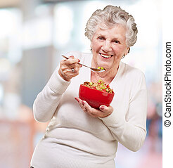 portrait of senior woman holding a cereals bowl indoor