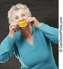 portrait of senior woman holding a orange slice in front of her mouth against a grunge wall