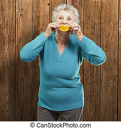 portrait of senior woman holding a orange slice in front of her mouth against a wooden wall