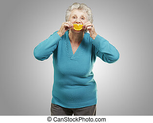 portrait of senior woman holding a orange slice in front of her mouth over grey background