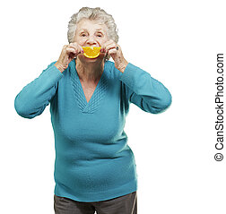 portrait of senior woman holding a orange slice in front of her mouth over white background