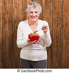 portrait of senior woman holding a cereals bowl against a wooden wall