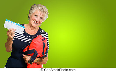 Portrait Of Senior Woman Holding Boarding Pass And Luggage...
