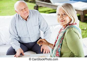 Portrait Of Senior Woman Holding Dominoes Cube