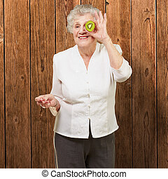 portrait of senior woman holding kiwi in front of her eye against a wooden wall