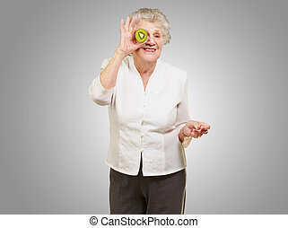 portrait of senior woman holding kiwi in front of her eye over grey background