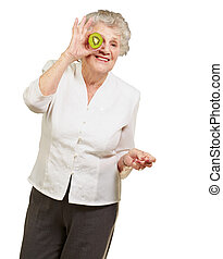 portrait of senior woman holding kiwi in front of her eye over white background