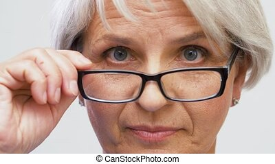 portrait of senior woman in glasses looking - vision and old...