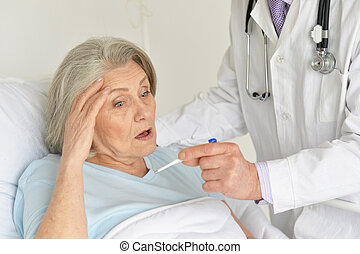 Portrait of senior woman in hospital with caring doctor