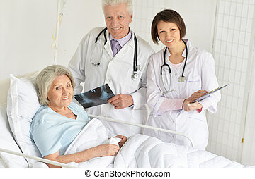 Portrait of senior woman in hospital with caring doctors