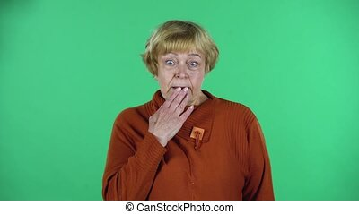Portrait of senior woman in a brown sweater and glasses is saying oops and shrugging expressing she is innocent, isolated over green background. Green screen. Chroma key.