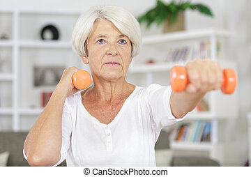 portrait of senior woman lifting dumbbells