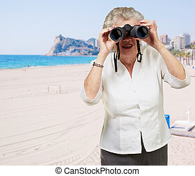portrait of senior woman looking through a binoculars in the beach