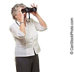 portrait of senior woman looking through a binoculars over white background