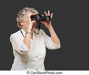 portrait of senior woman looking through a binoculars over black background