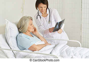 Portrait of senior woman portrait in hospital with caring doctor