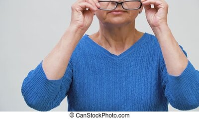 portrait of senior woman putting her glasses on - vision and...