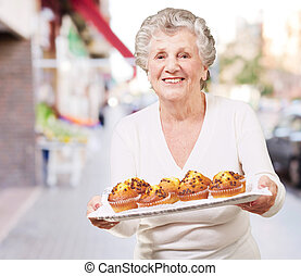 portrait of senior woman showing a chocolate muffin tray at street